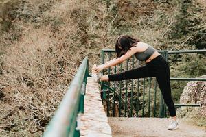 Jeune femme sur des vêtements de sport étirant sa jambe sur un trottoir au milieu d'une forêt d'automne tout en souriant à l'espace de copie de l'appareil photo