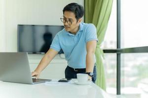 homme d & # 39; affaires dans des verres penché sur la table et travailler sur un ordinateur portable au bureau photo