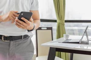 homme d & # 39; affaires travaillant sur un téléphone portable avec un ordinateur portable sur la table photo