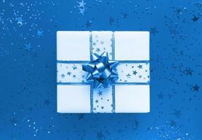 boîte-cadeau et étoiles sur fond bleu plat monochrome photo