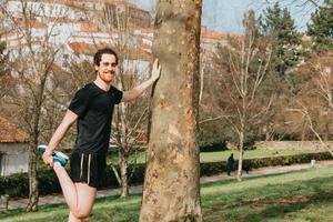 Un jeune homme étirant sa jambe contre un arbre tout en s'entraînant au parc avec copie espace photo