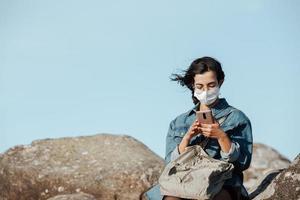 Une jeune femme portant un masque vérifiant son téléphone pendant que le vent souffle avec copie espace photo
