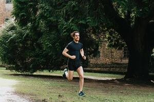 Un jeune homme faisant un sprint dans le parc au cours d'une journée d'entraînement tout en faisant du fitness photo