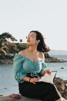 Jeune femme lisant à la plage pendant un super coucher de soleil tout en utilisant un masque se détendre et des concepts inspirants avec copie espace style de vie coloré photo