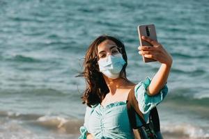 Jeune femme sur la plage à l'aide d'un masque tout en prenant un style d'été selfie lifestyle concept photo