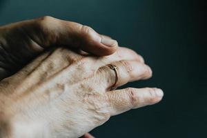 une paire de vieilles mains montrant avec une bague photo