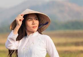Portrait femme vietnamienne dans une robe blanche portant un ao dai marchant joyeusement dans la prairie du soir photo