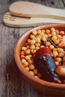 Saucisse de pois chiches et bacon dans une mijoteuse par cuillère et fourchette en bois photo