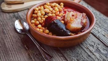 Saucisse de pois chiches et bacon dans une mijoteuse par cuillère et fourchette en bois et une petite cuillère en métal photo