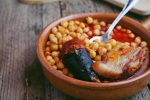 saucisse de pois chiches et bacon dans une mijoteuse par une petite cuillère en métal photo