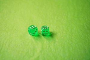 Une macro monochromatique dynamique avec profondeur de champ sur deux dés de jeu en verre vert avec deux chanceux numéro six sur fond vert photo