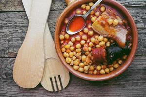 Plat de saucisse de pois chiches et bacon dans une mijoteuse par cuillère et fourchette en bois photo