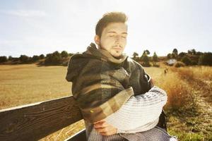 Jeune homme aux yeux fermés profitant du soleil d'automne du matin avec le rétroéclairage du ciel bleu photo