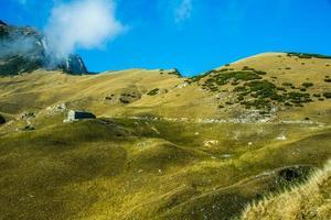 hutte parmi les champs d'automne jaune sur l'un des alpes photo