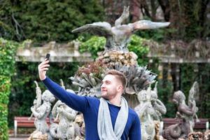 Jeune homme prenant une photo avec son téléphone portable dans le parc