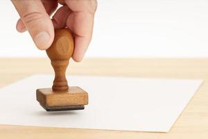 main tenant un tampon en caoutchouc et papier vierge sur table en bois photo