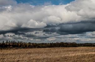 nuages sombres et champs bruns photo