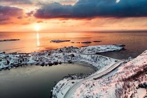 Paysage couvert de neige sur reine dans les îles Lofoten au coucher du soleil photo