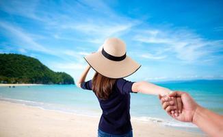 femme tenant la main de son mari tout en courant ensemble sur la plage photo