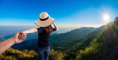 femme tenant la main de son mari tout en courant ensemble sur la montagne photo