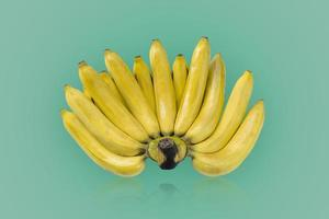 Groupe de bananes mûres de couleur jaune isolé sur fond de couleurs vertes photo