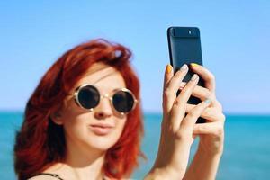 Femme rousse prend selfie sur la caméra du smartphone photo
