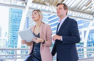 les hommes et les femmes d'affaires parlent du marché des affaires et tiennent des ordinateurs portables photo