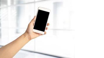Femme asiatique active lady holding mobile phone pour communiquer sur le travail au bureau moderne photo