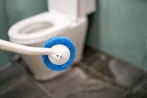 femme de chambre nettoyage cuvette des toilettes avec brosse dans la salle de bains à la maison photo