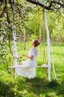 Jeune mariée aux cheveux blonds en déshabillé blanc à l'aide de parfum sur une balançoire en corde photo