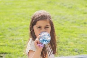petite fille boit de leau dans une bouteille en plastique photo