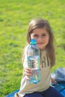 petite fille tient une bouteille deau photo