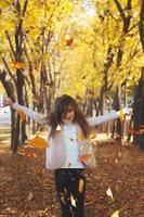 belle petite fille jetant des feuilles mortes jouant dans le parc automne nature fond photo