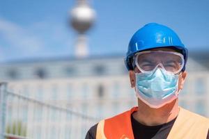 travailleur de la construction portant un casque bleu, gilet réfléchissant et masque chirurgical de protection photo