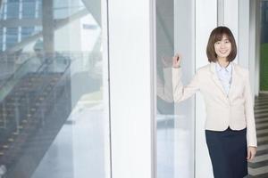 Jolie femme d'affaires asiatique souriant à l'extérieur du bureau photo