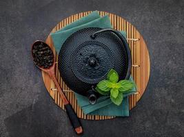 Théière en fonte noire avec tisane mis en place sur fond de pierre sombre photo