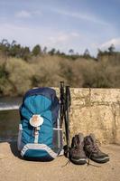 Sac à dos avec coquillage, symbole du camino de santiago avec des bottes de randonnée et des bâtons s'appuyant sur un mur de pierre photo