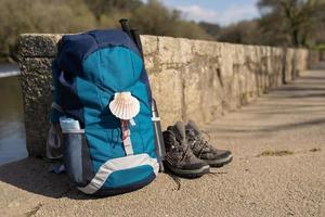 Sac à dos et bottes de randonnée s'appuyant sur un mur de pierre photo