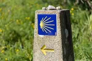 Camino de santiago signe sur monolithe de pierre avec fond d'herbe verte photo
