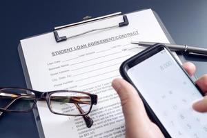 Demande de prêt étudiant vierge sur table et main tenant un smartphone avec application de calculatrice photo