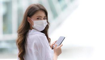 Portrait de jeune femme avec visage souriant à l'aide d'un téléphone se promène dans une ville photo