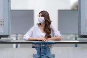 Portrait de jeune femme avec visage souriant portant un masque facial promenades de protection dans une ville photo