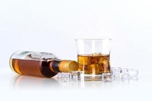 Verre de whisky avec des glaçons et une bouteille sur fond blanc photo