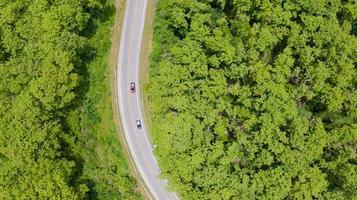 Vue de dessus aérienne voiture roulant à travers la forêt sur route de campagne photo