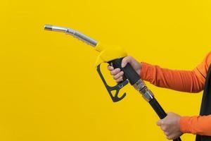 Femme tenir la buse de carburant sur fond jaune photo