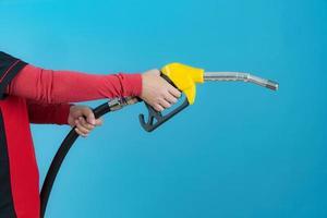Femme tenir la buse de carburant sur fond bleu photo