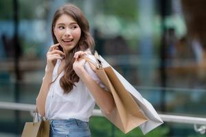 portrait en plein air de femme heureuse tenant des sacs à provisions et visage souriant photo