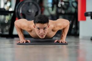 Formation homme sport faisant des exercices de push ups dans une salle de fitness photo