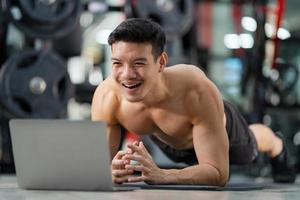 Formation en ligne sport homme formation faisant des push ups exercice avec ordinateur portable dans la salle de fitness photo