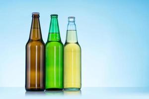 Groupe de trois bouteilles de bière sur fond bleu photo